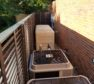 Horizontal louvered equipment enclosure installed around residential heating and cooling equipment