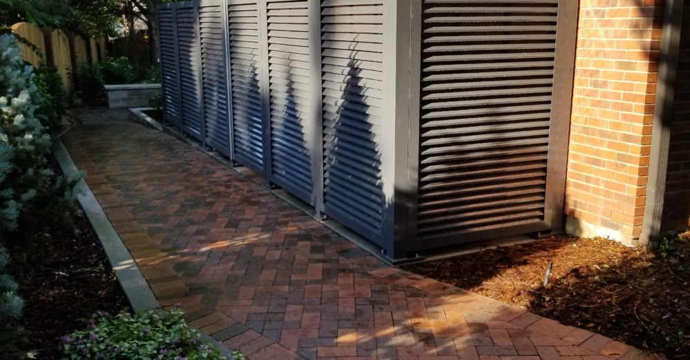 Residential home with louvered screen enclosure around heating equipment