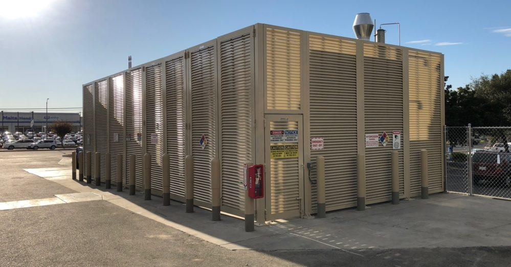 12 foot tall aluminum horizontal louvered enclosure painted khaki with several warning signs installed to instill caution