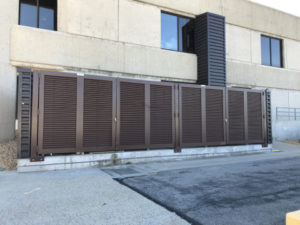 Dark brown louvered architectural swing gate