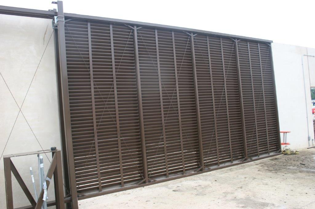 Extra tall brown industrial cantilever gate with louvered screening