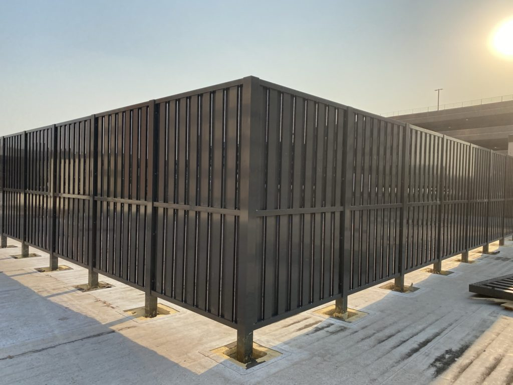Alternating rooftop screening providing a formidable appearance with large tubular louvers running vertically or horizontally in a shadow box pattern.