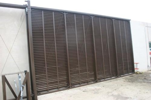Brown louvered industrial cantilever gate